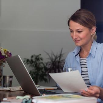Frau, die papier hält und laptop betrachtet