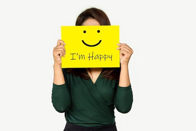 Frau, die papier mit wort hält ich bin glücklich und lächelndes gesicht
