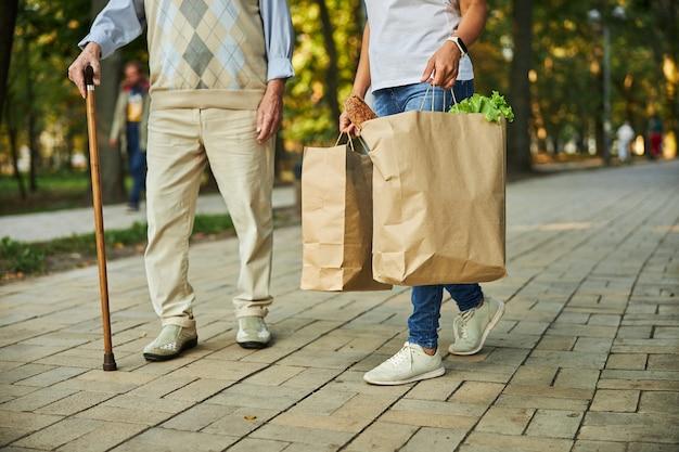 Frau, die papiereinkaufstaschen in der hand nahe dem älteren mann hält