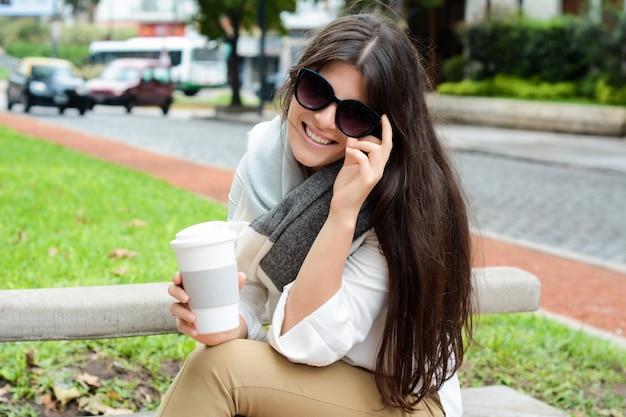 Frau, die papierkaffeetasse in der straße hält.