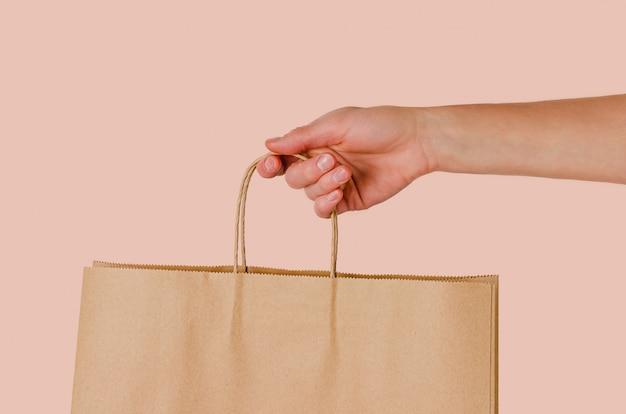 Frau, die papiertüte in der hand auf rosa hintergrund hält. einkaufs- und verkaufskonzept