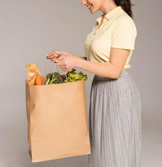 Frau, die papiertüte mit gemüse nah oben hält