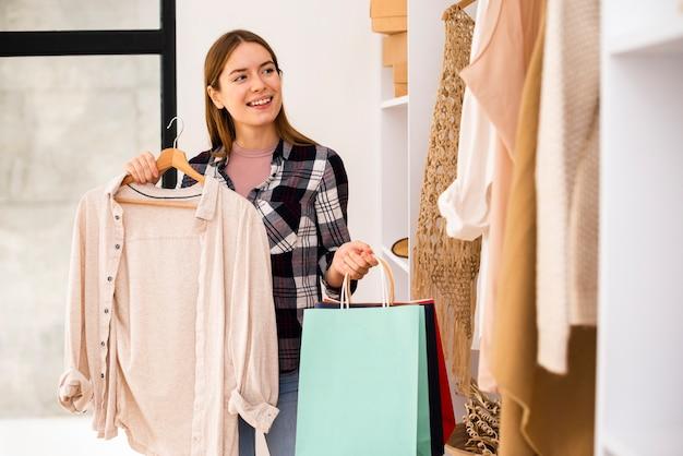 Frau, die papiertüten hält und in einer garderobe schaut