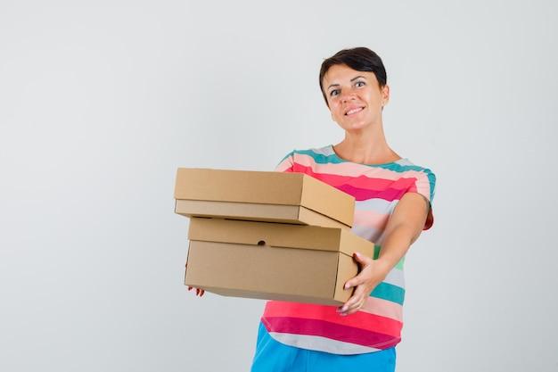 Frau, die pappkartons im gestreiften t-shirt präsentiert und fröhlich schaut