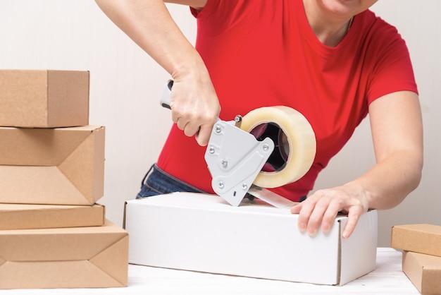 Frau, die pappkartons unter verwendung des bandspenders verpackt