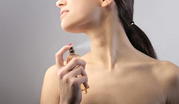Frau, die parfüm anwendet