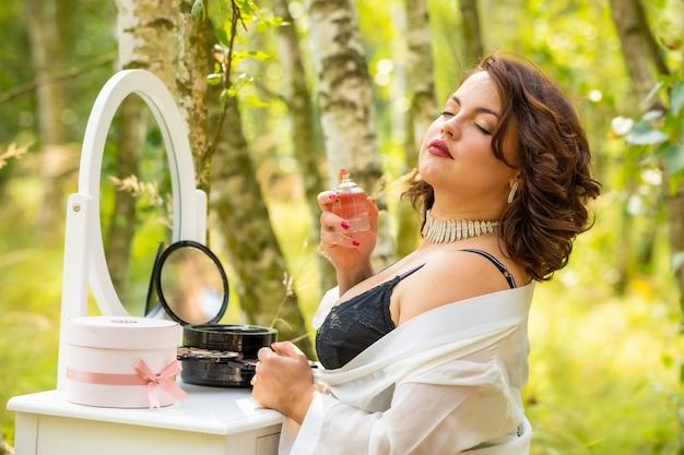 Frau, die parfüm im wald sitzt und verwendet