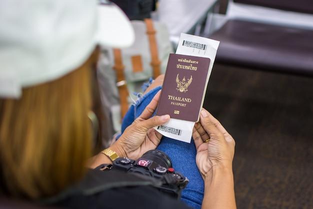 Frau, die pass hält und am flughafen auf reisereise wartet. weicher fokus.