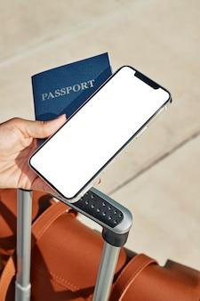 Frau, die pass und smartphone mit gepäck am flughafen während der pandemie hält