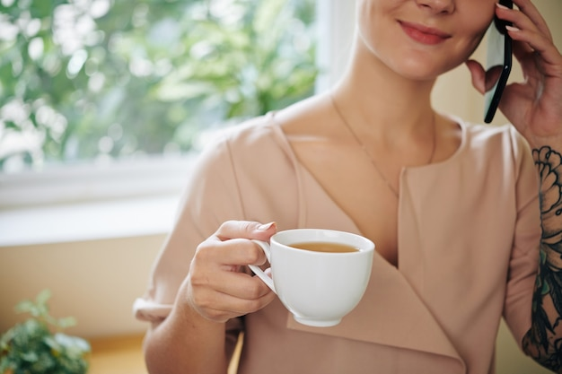 Frau, die pause macht, mit dem telefon spricht und kaffee trinkt