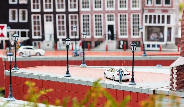 Frau, die per telefon nahe dem auto auf dem pier, miniaturszene im freien, europa spricht. mini-figuren mit hoher entkalkung von objekten, realistisches diorama