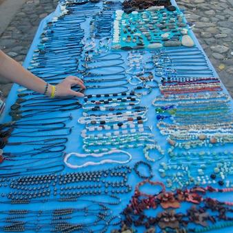 Frau, die perlenbesetzte halskette am marktstall, copan, copan ruinas, honduras wählt