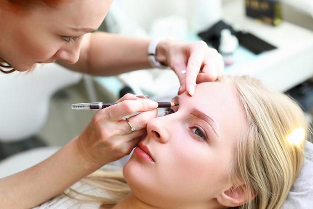 Frau, die permanentes make-up macht