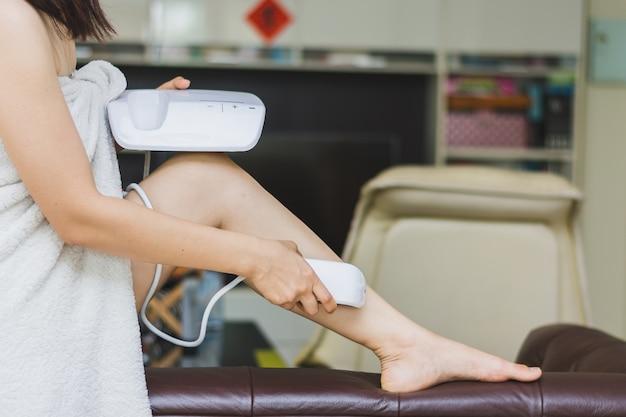 Frau, die persönliche ipl-laseepilation verwendet, bereiten sich für hautpflege zu hause vor