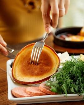 Frau, die pfannkuchen mit gabel und messer nimmt, diente zum frühstück