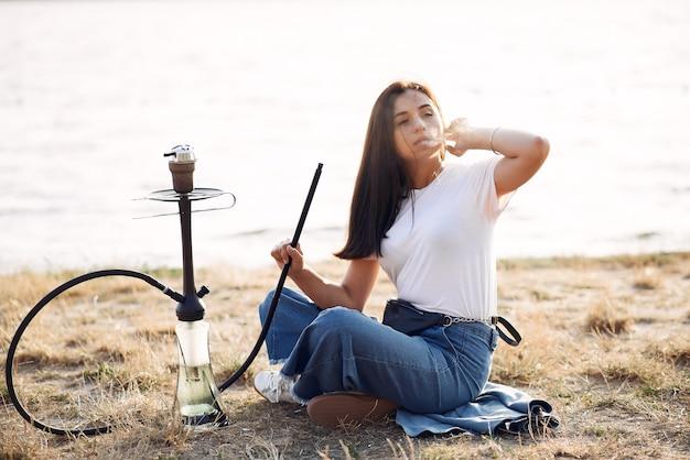Frau, die pfeife und rauchende shisha am strand hält