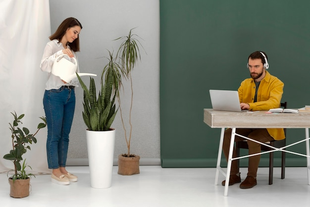 Frau, die pflanze und mann mit laptop wässert