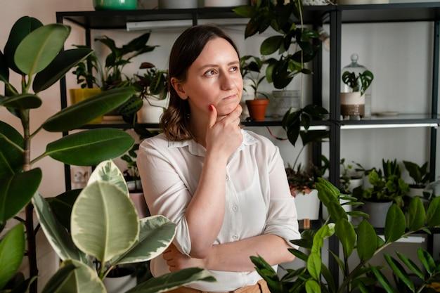 Frau, die pflanzen zu hause wächst