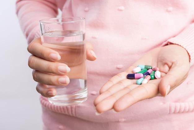 Frau, die pille und eine andere hand ein glas sauberes mineralwasser anhalten.