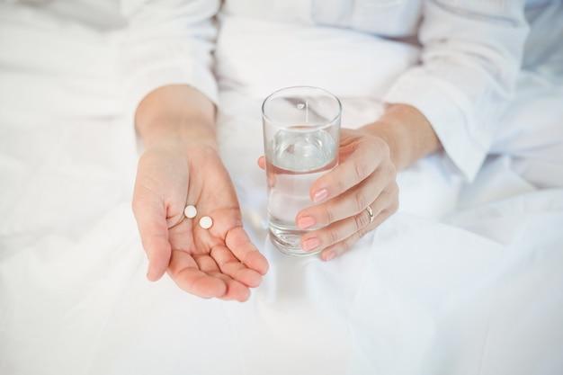 Frau, die pillen und trinkglas hält