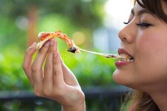 Frau, die Pizza an der Gaststätte isst