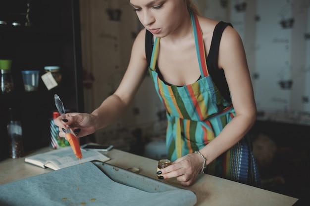 Frau, die pizza an der küche kocht