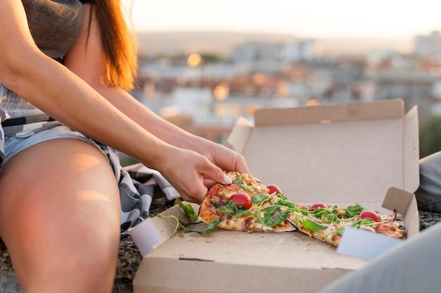 Frau, die pizza draußen isst