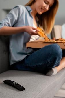 Frau, die pizza isst, während fernsehen nah oben betrachtet