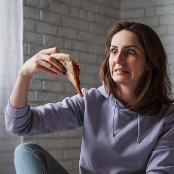 Frau, die pizza zu hause isst
