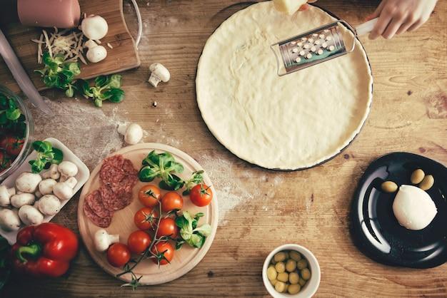 Frau, die pizza zubereitet
