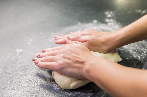 Frau, die pizzateig auf schwarzem granittisch vorbereitet