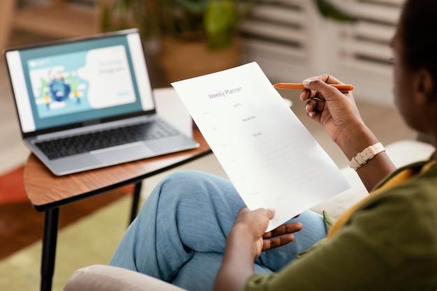 Frau, die pläne macht, das haus mit laptop zu renovieren