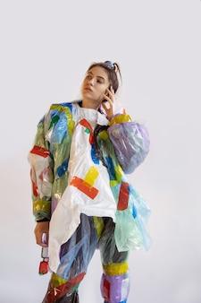Frau, die plastik auf weißer wand trägt. weibliches modell in kleidern und schuhen aus müll. mode-, stil-, recycling-, öko- und umweltkonzept. zu viel verschmutzung, wir essen und nehmen es.
