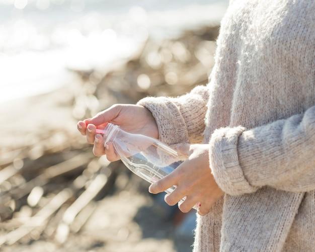 Frau, die plastikflasche vom sand auswählt
