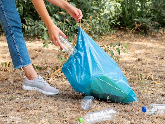 Frau, die plastikflaschen in der tasche für die wiederverwertung sammelt