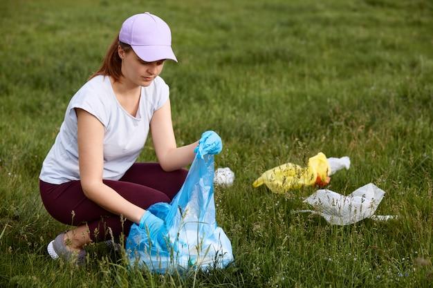 Frau, die plastikflaschen und müll von der wiese aufnimmt, umweltaktivist, der plastikmüll sammelt, freiwilliger, der einzelnes gebrauchtes plastik im grünen feld aufhebt.