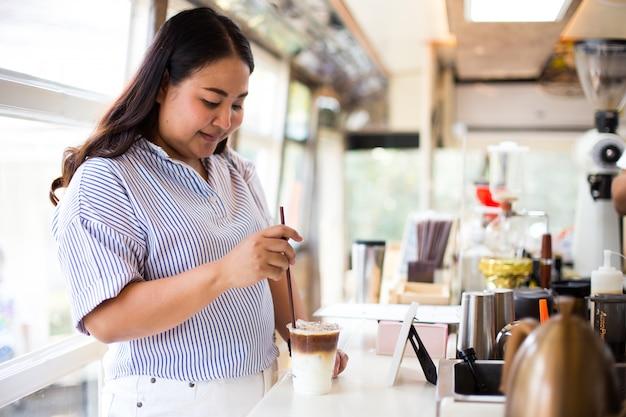 Frau, die plastikglas eiskaffee mit milch hält
