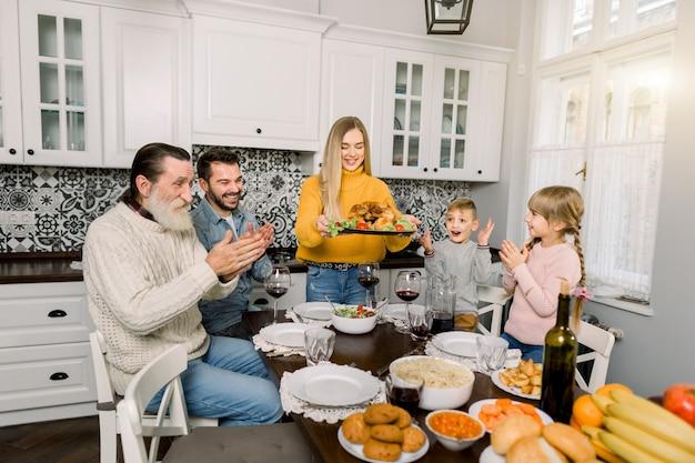 Frau, die platte mit gebratenem truthahn hält und für familienessen zu hause garniert. alle familienmitglieder sitzen aufgeregt, glücklich und applaudierend am tisch