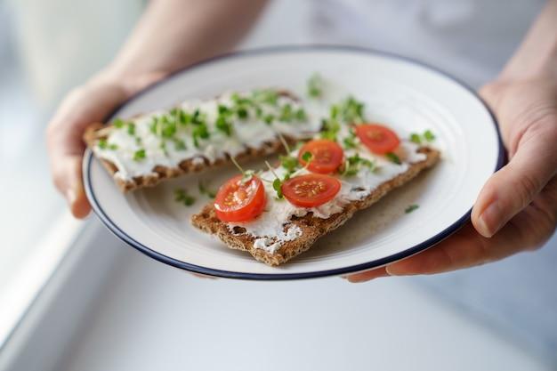 Frau, die platte mit roggen-knäckebrot mit cremigem vegetarischem käsetofu, tomate, mikrogrün hält