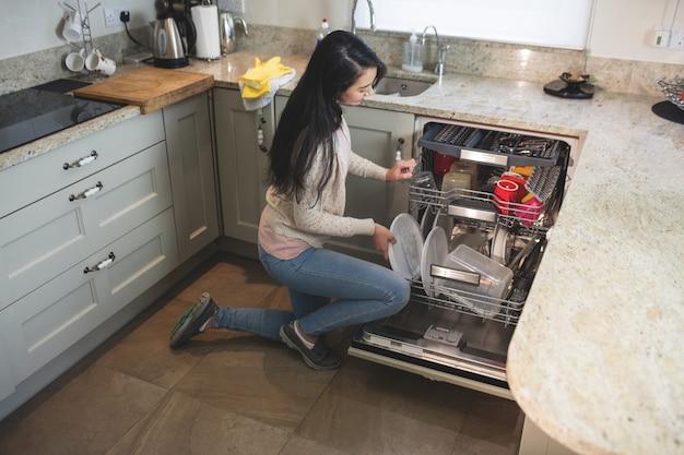Frau, die platten in der spülmaschine anordnet