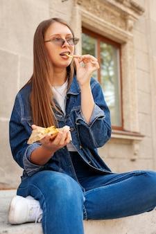 Frau, die pommes frites im freien isst