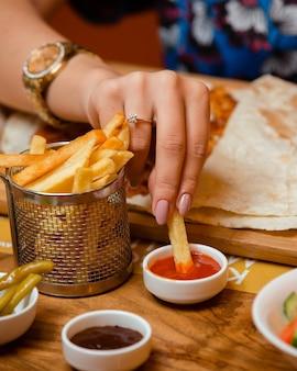 Frau, die pommes frites in ketchup im restaurant eintaucht