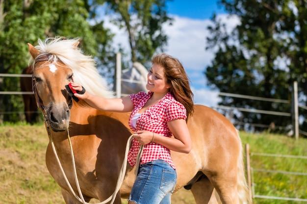 Frau, die pony auf pferdestall kämmt