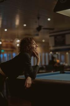 Frau, die pool an einer bar spielt