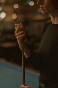 Frau, die pool an einer stange spielt