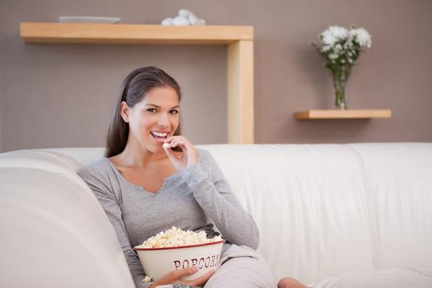 Frau, die popcorn beim überwachen des films isst