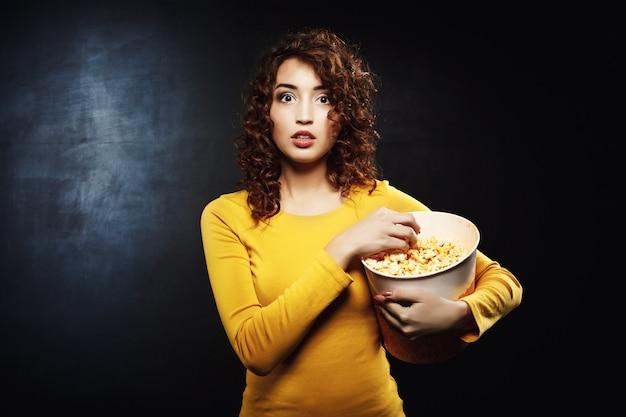 Frau, die popcorn isst, während sie film an der straßenschau sieht