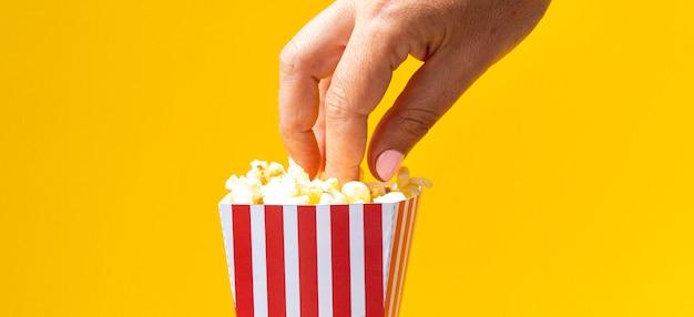 Frau, die popcorn vom kasten isst