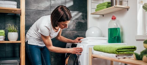 Frau, die programm auf waschmaschine wählt