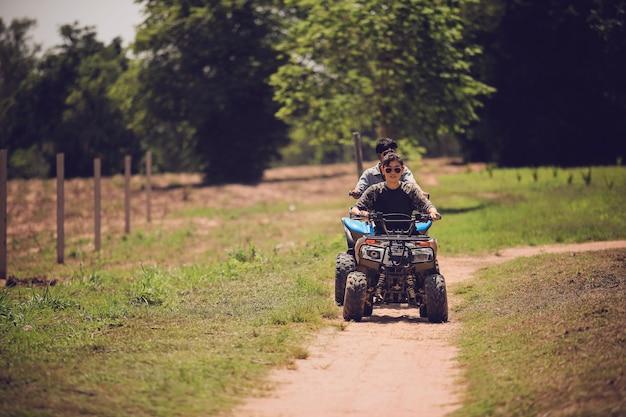 Frau, die quad atv-fahrzeug läuft auf schmutzfeld reitet